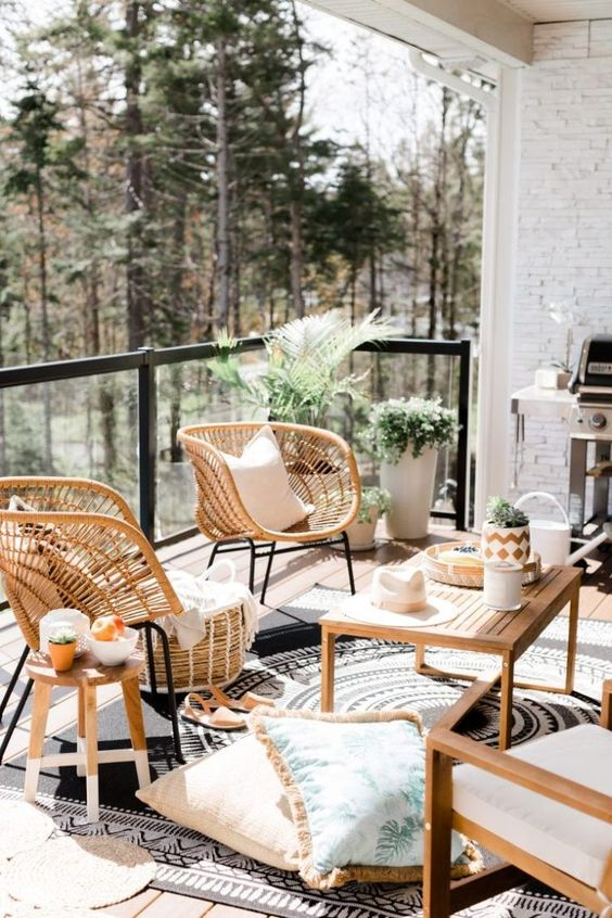 un ampio e accogliente balcone con mobili in legno e vimini, piante in vaso, una griglia e alcuni tessuti accoglienti