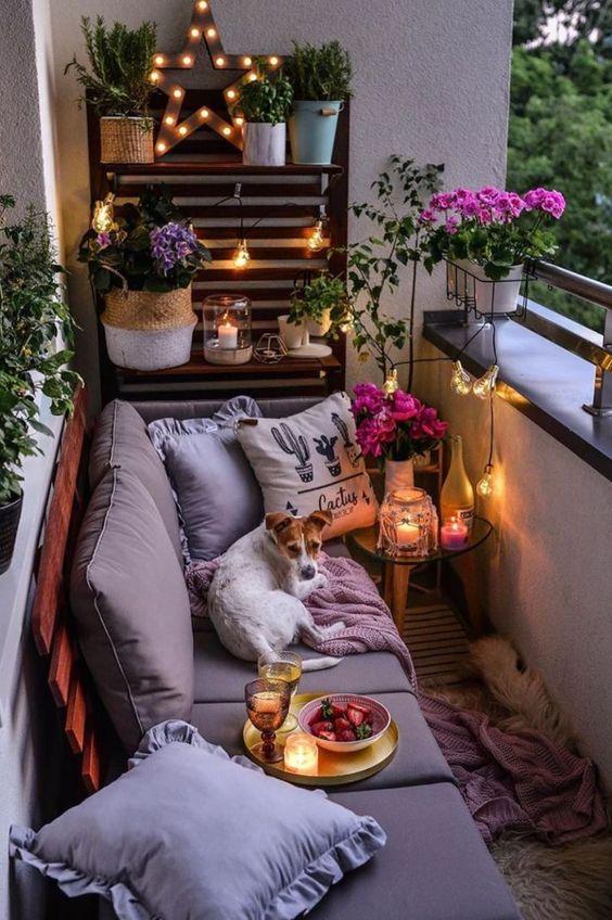un piccolo balcone accogliente con una parete di pallet e un divano, alcuni fiori in vaso e vegetazione e lanterne a candela