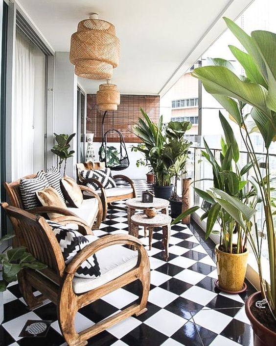 un ampio balcone con piastrelle bianche e nere, mobili in legno, lampade in vimini e cuscini stampati e molte piante