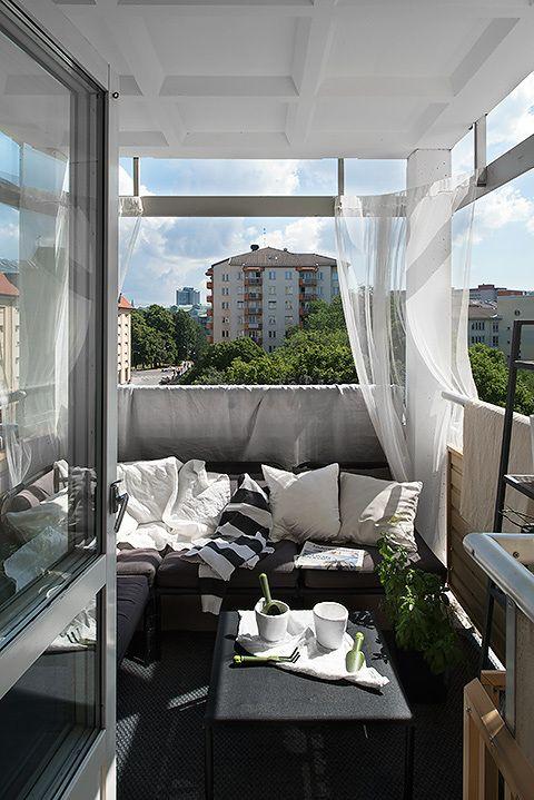 un balcone monocromatico con mobili scuri, tessuti stampati, tende trasparenti e vegetazione in vaso