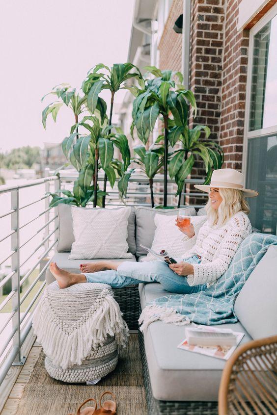un balcone boho neutro con mobili in vimini, tappezzeria neutra, vegetazione in vaso e tessuti boho per più intimità