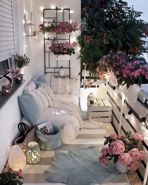 un balcone neutro e pastello con tessuti boho, lanterne a candela, vegetazione in vaso e luci