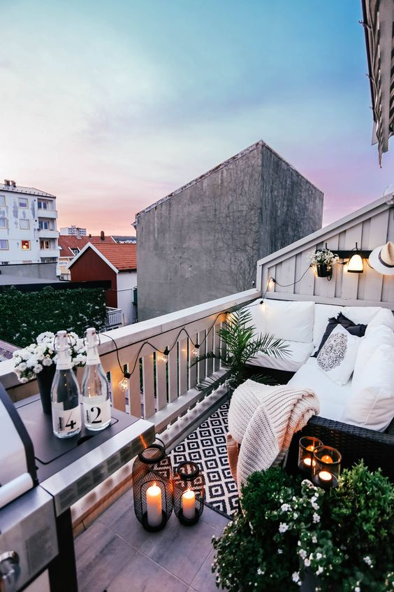 un balconcino monocromatico con mobili in vimini nero, lanterne a candela, piante e fiori in vaso e una griglia