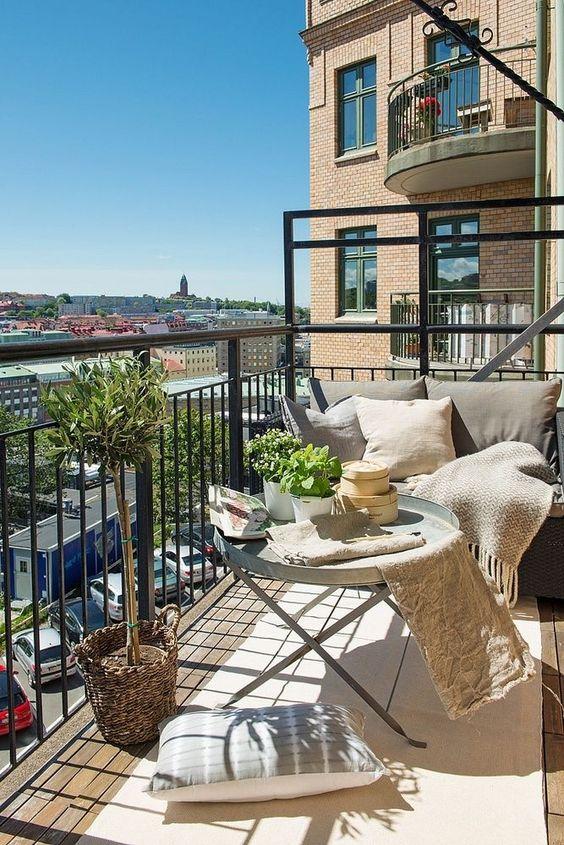 un balcone neutro con mobili in metallo, tessuti neutri, piante in vaso e molti cuscini è molto accogliente
