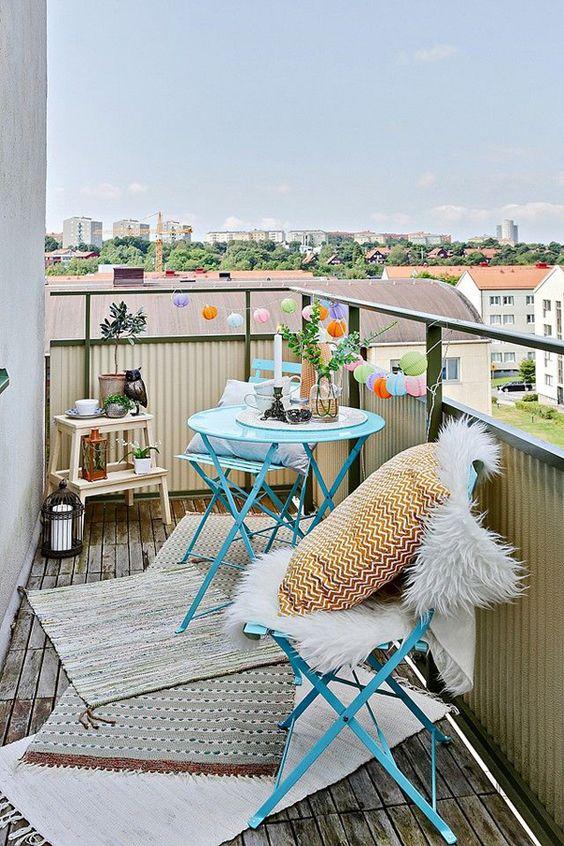 uno spazio piccolo e carino con mobili in metallo blu, tappeti a strati, cuscini stampati, luci, lanterne a candela e vegetazione