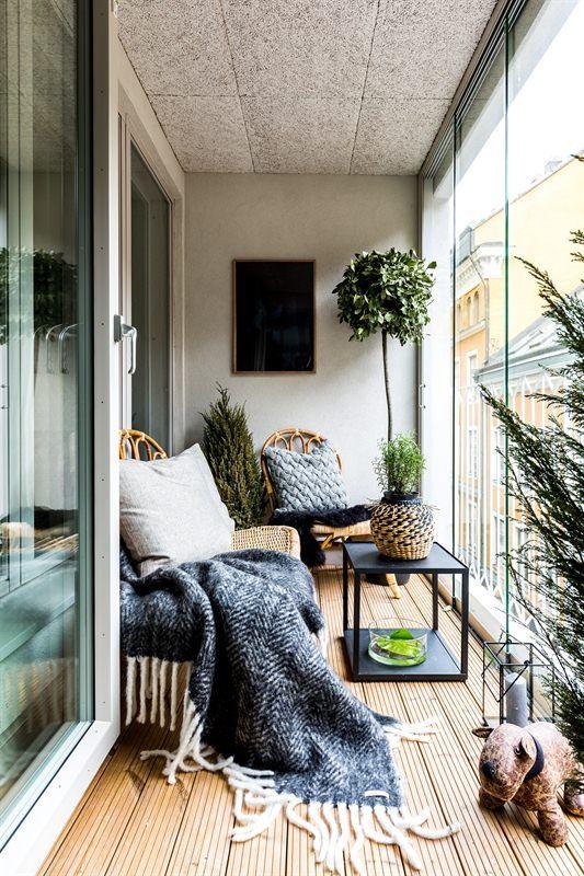 un balcone nordico con mobili in rattan, tessuti stampati, piante in vaso e lanterne a candela per uno spazio chic