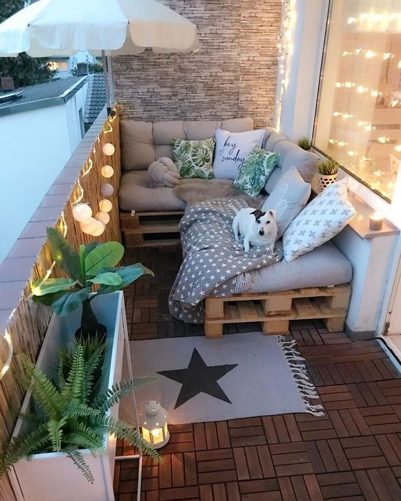 un piccolo e accogliente balcone con divano a forma di L di pallet, cuscini stampati, piante in vaso, luci e lanterne a candela