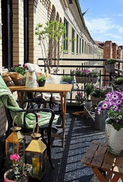 un rinfrescante balcone estivo con piante in vaso e fiori, mobili in rattan e legno, lanterne a candela e tessuti