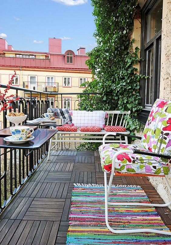 un balcone semplice e colorato con tessuti luminosi, alcuni mobili in metallo e tavoli con ringhiera e vegetazione