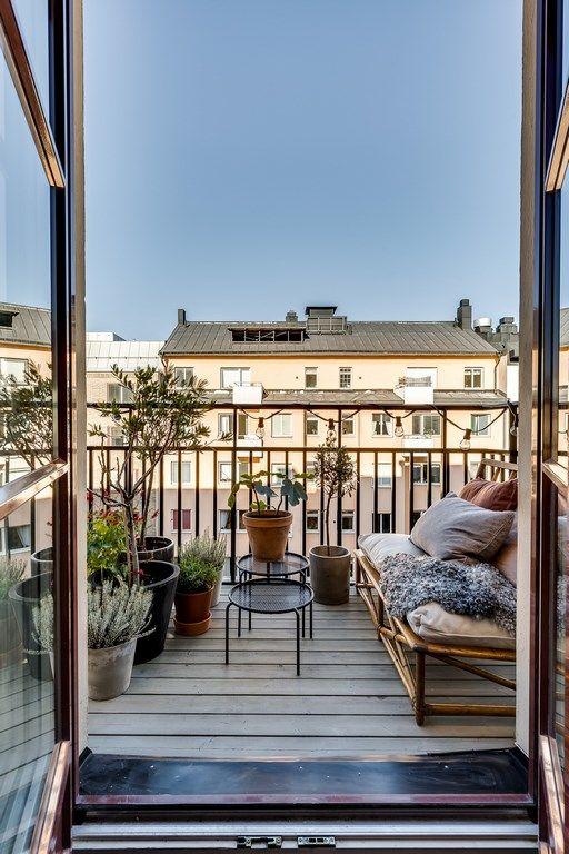 un balcone semplice e naturale con un divano in rattan, molti cuscini e coperte, piante in vaso e altre piante