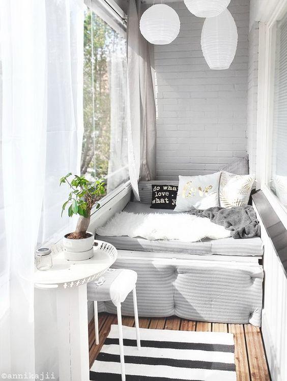 un piccolo balcone con un divano letto, un tavolino e uno sgabello, lanterne di carta e tende trasparenti è molto accogliente