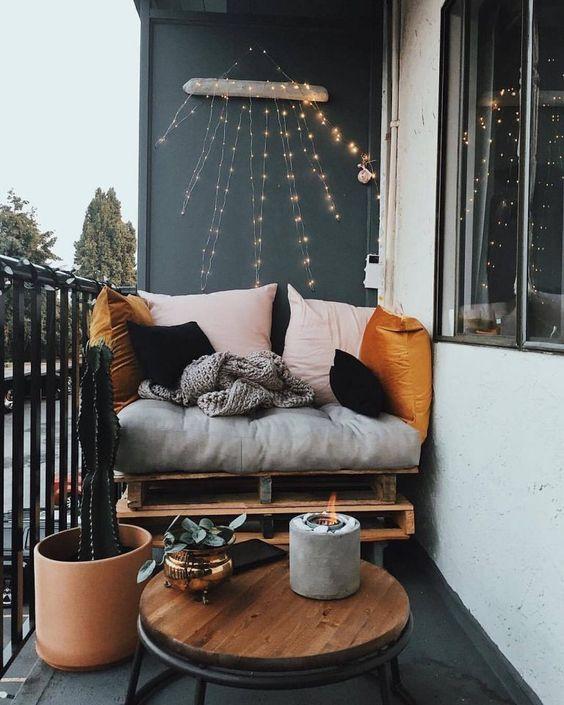un balcone piccolo ma chic con un sedile per pallet, cuscini colorati, un tavolo, un cactus e una candela in un candelabro di cemento