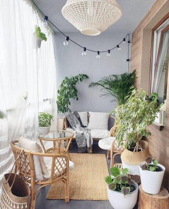 un piccolo balcone con tende trasparenti, luci, una lampada di vimini, mobili in rattan, piante importanti e cesti è molto accogliente