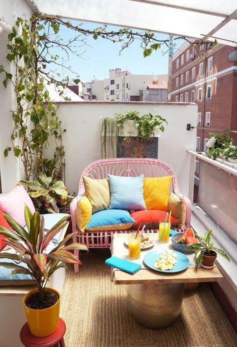un piccolo balcone luminoso con un divanetto rosa, un tavolino, una panca bianca con ripostiglio, vegetazione in vaso e cuscini luminosi