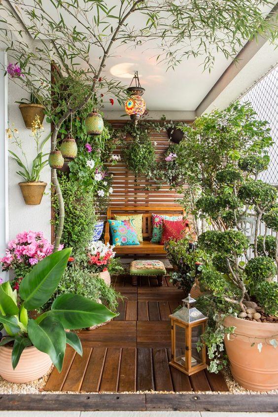 un balcone estivo trasformato in giardino, con fiori in vaso e vegetazione, lanterne a candela e alcuni mobili in legno