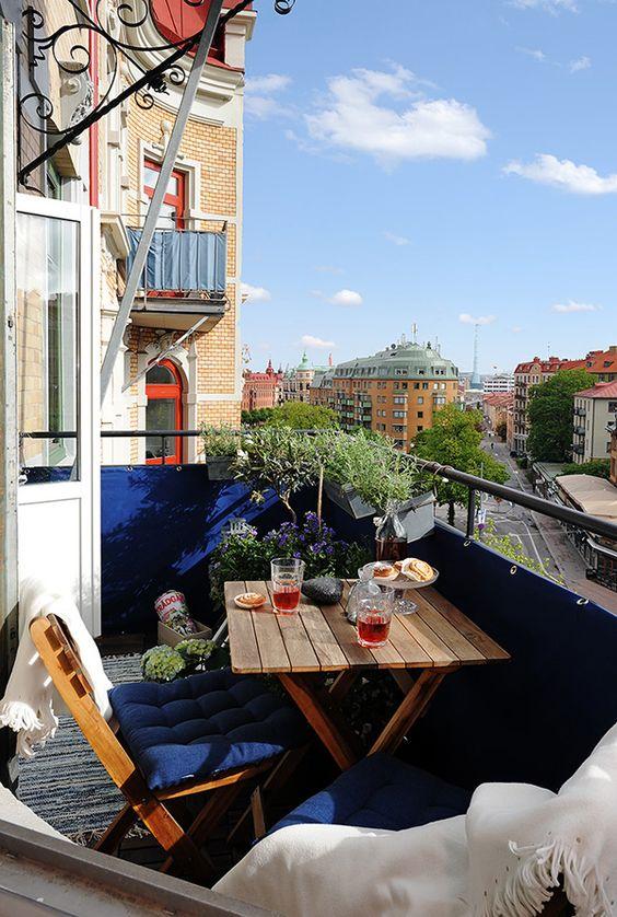 un piccolo balcone con ringhiera e tappezzeria blu scuro, piante in vaso e fiori e mobili pieghevoli in legno