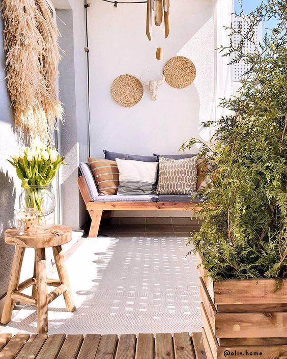 un balcone estivo in colori neutri, con mobili in legno, vasi per casse con vegetazione, cesti decorativi, erba di pampa e cuscini stampati