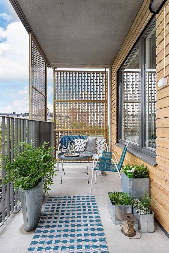 uno spazio minuscolo e accogliente con piante di metallo con vegetazione, mobili in metallo e vimini e tocchi di blu