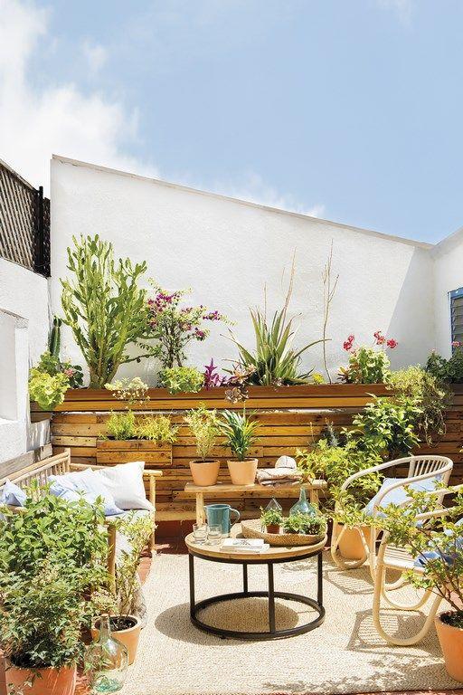 uno spazio estivo con una parete in legno, mobili in rattan e molta vegetazione in vaso e fiori per un'atmosfera da giardino