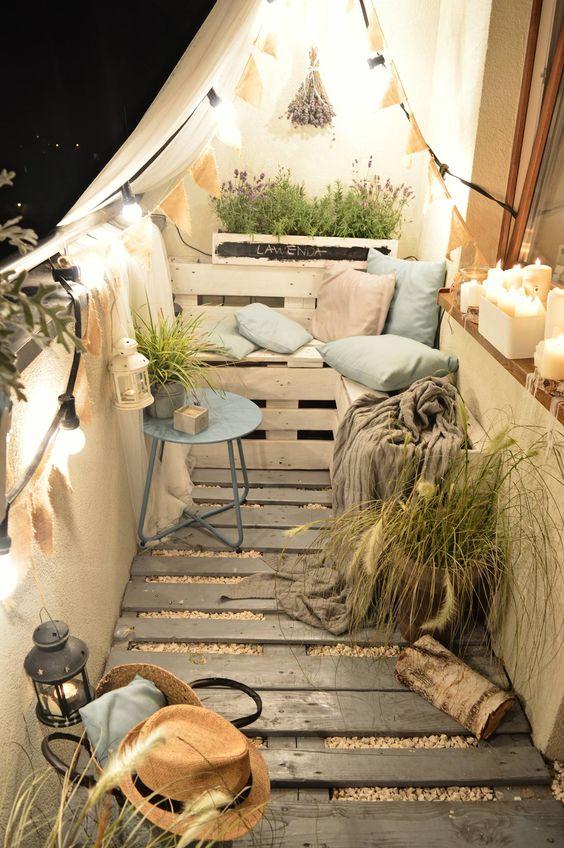 un balcone minuscolo e accogliente con pavimento in legno, mobili e pentole per pallet, vegetazione in vaso e fiori, luci e candele