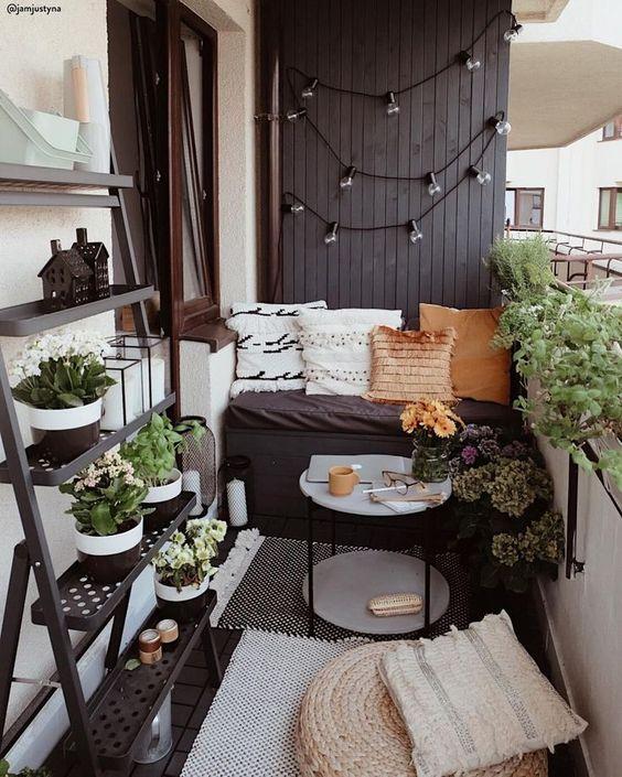 un minuscolo balcone monocromatico con pareti bianche e nere, mobili blakc, vegetazione in vaso e fiori e vari cuscini e tappeti