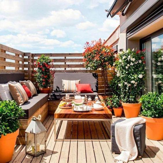 un balcone estivo con un ponte e mobili in legno, fiori in vaso e vegetazione e cuscini luminosi più lanterne a candela