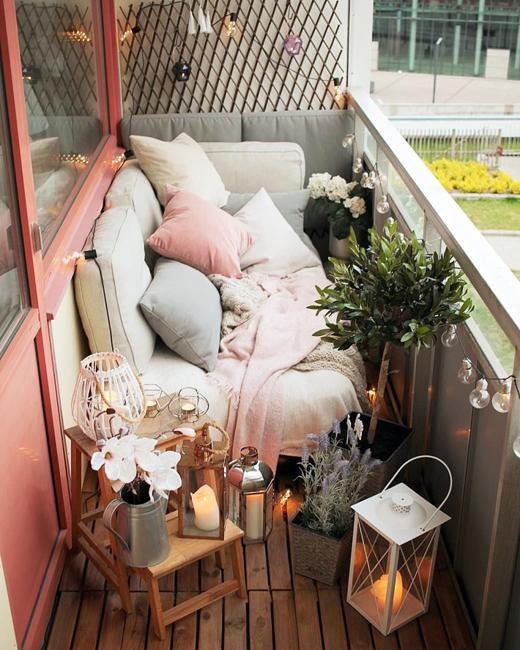 un minuscolo balcone stretto con tessuti e cuscini color pastello, piante in vaso e fiori, lanterne a candela e mobili in legno
