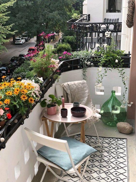 un minuscolo balcone estivo con un sacco di fiori in vaso, mobili in legno e metallo e graziosi accessori