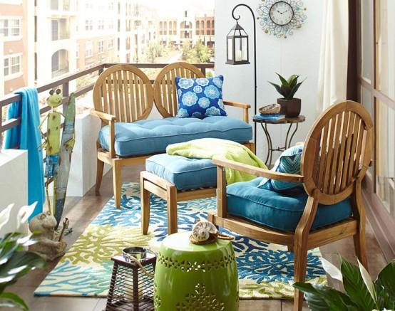 un balcone estivo luminoso e allegro fatto in blu e verde, con mobili chic di ispirazione vintage e tessuti luminosi