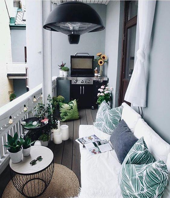 un balcone accogliente con un divano bianco a forma di L, cuscini stampati, una griglia, piante in vaso e fiori