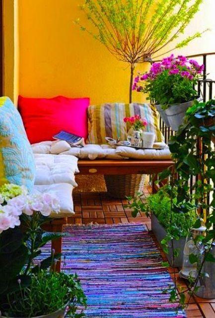 un balcone estivo luminoso e colorato con pareti gialle, panchine con cuscini luminosi, tappeti e piante e fiori in vaso