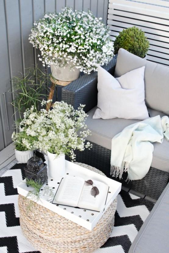 un balcone estivo monocromatico con mobili in vimini neutri e neri, tappezzeria neutra, fiori in vaso e vegetazione e stampe geometriche