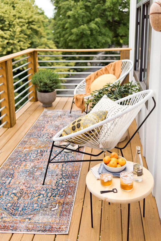 un invitante balcone estivo con un tappeto boho, alcune sedie rotonde, un tavolo e piante in vaso più cuscini