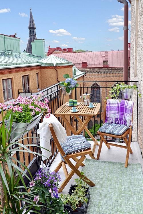 un allegro balcone estivo con tessuti luminosi, fiori in vaso e vegetazione e semplici mobili pieghevoli in legno
