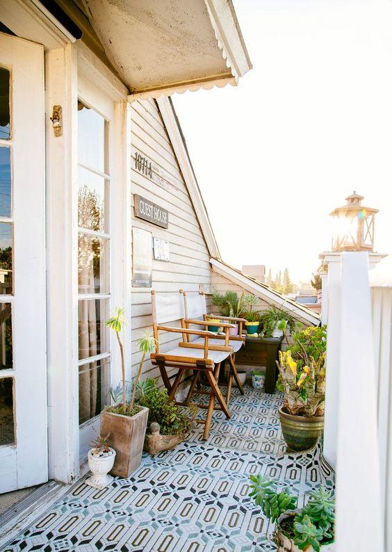 un minuscolo balcone accogliente con un tappeto luminoso, sedie pieghevoli, piante in vaso e fiori per godersi un caffè