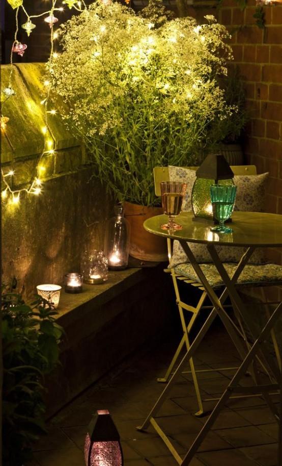 arredamento semplice del balcone estivo con piante in vaso e fiori, con candele e luci e mobili vintage in metallo