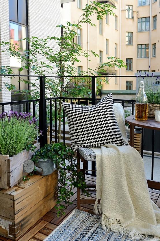 un accogliente balcone estivo con casse di legno con vegetazione e fiori, mobili pieghevoli in legno e tessuti neutri