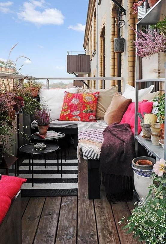 un luminoso balcone estivo con pavimento in legno scuro, mobili in legno scuro, vegetazione in vaso e fiori e tessuti luminosi