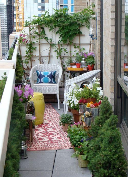 un luminoso balcone estivo con molta vegetazione e fiori in vaso, con tappeti luminosi e mobili in vimini bianco, tessuti e accessori luminosi