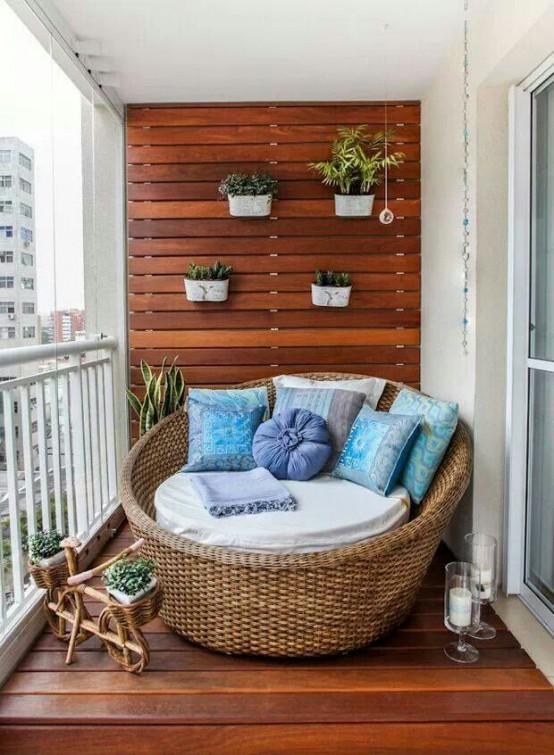 un balcone contemporaneo rivestito di legno tinto, con una sedia di vimini, piante in vaso, piante grasse e tessuti luminosi