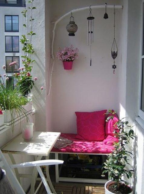 un piccolo balcone estivo in bianco, con tocchi rosa e fucsia luminosi, fiori in vaso e vegetazione e lanterne a candela boho