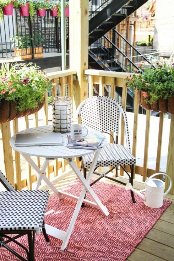 un piccolo e luminoso balcone estivo con sedie in legno scuro, un tavolo bianco, un tappeto luminoso e piante in vaso e fiori sulle ringhiere