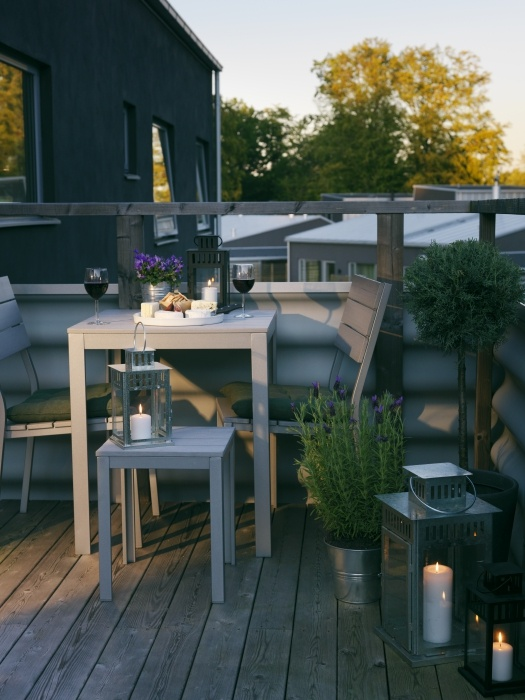 un piccolo e accogliente balcone estivo con mobili in legno grigio, piante in vaso e fiori e lanterne a candela