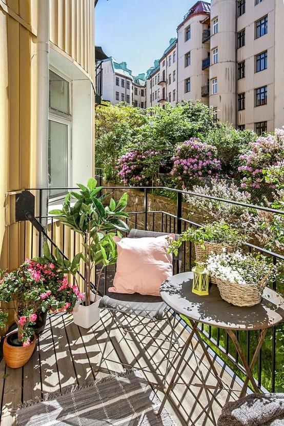 un minuscolo balcone con molta vegetazione in vaso e fiori e alcuni mobili in metallo più alcuni cuscini