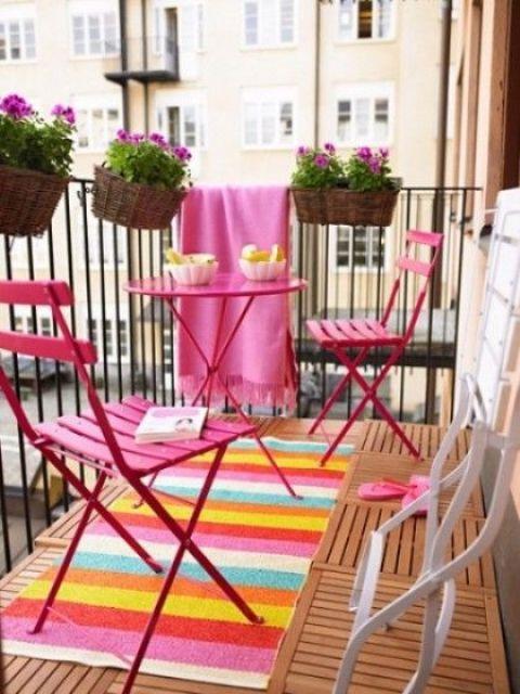 un piccolo e luminoso balcone estivo con un tappeto e una coperta luminosi, mobili rosa audaci e fiori in vaso