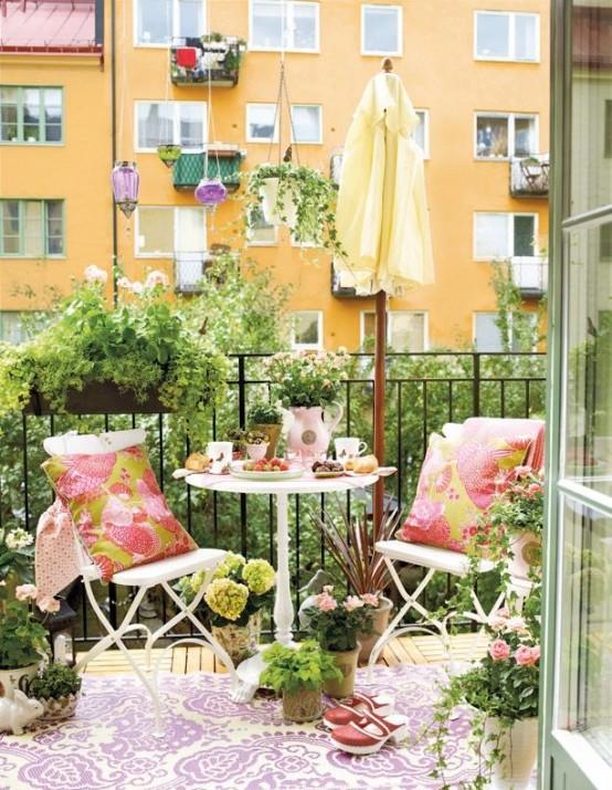 un accogliente balcone estivo con semplici mobili in metallo bianco, tessuti stampati colorati, fiori in vaso e vegetazione