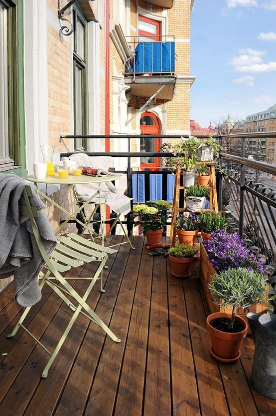 un piccolo balcone con mobili pieghevoli in metallo e piante in vaso e fiori è uno spazio semplice e accogliente per godersi l'aria fresca