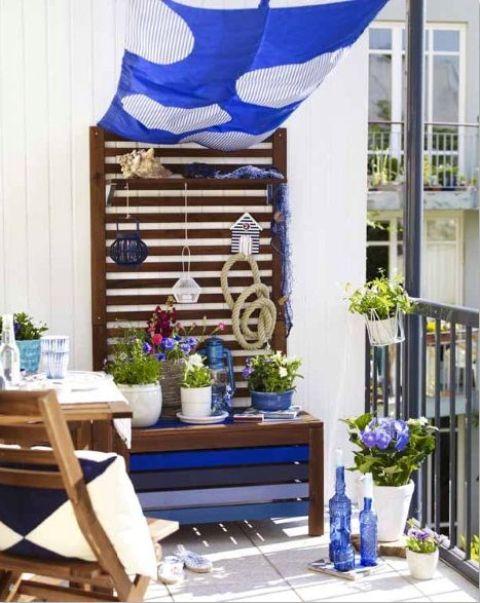 un balcone estivo ispirato al mare con tessuti blu, una panchina dipinta, fiori in vaso, bottiglie blu e cuscini
