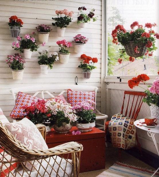 un balcone vintage super luminoso in bianco, con molto rosso, fiori in vaso e vegetazione e tessuti stampati luminosi per un look audace