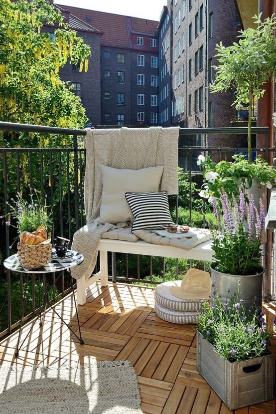 un balcone estivo nordico con una panchina bianca, un tavolo di metallo, piante in vaso e fiori, tessuti neutri e stampati